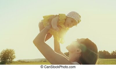 Happy mom holding her cute baby girl while walking on the summer field
