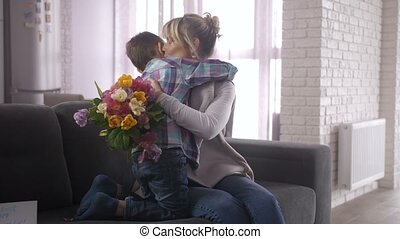 Joyful adult mother with huge bouquet of multicolored tulip flowers tightly embracing and kissing preadolescent boy sitting on sofa in living room. Loving woman thanking son for Mother's day greetings