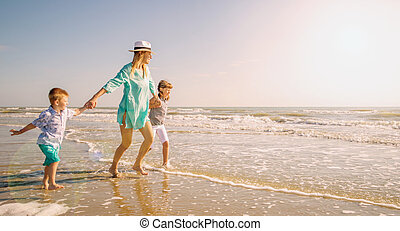 happy mom playing whit her children with the sea
