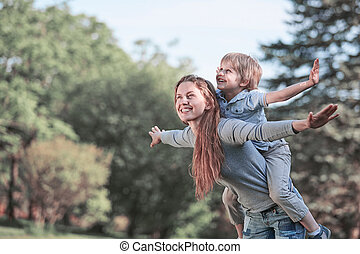 happy mom playing with her son in the summer Park .