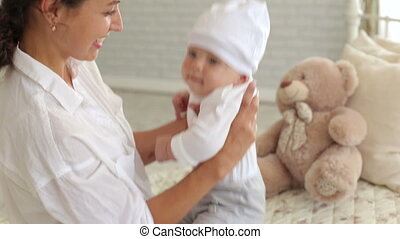 Happy mom plays with her little newborn son at home.