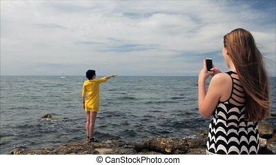 Happy mom taking photo your daughter with smartphone on the see background