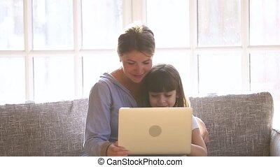 Happy mom with child daughter having fun enjoying using laptop