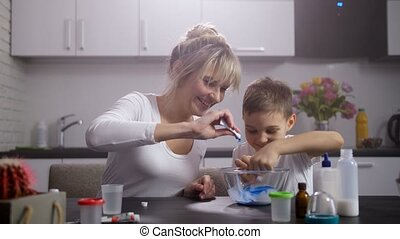 Happy mom with son making slime in home kitchen - Joyful...