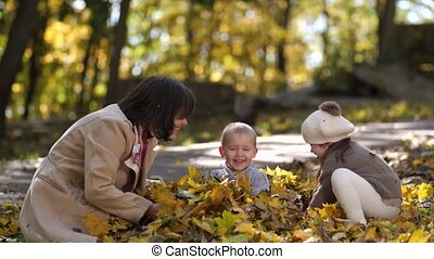 Happy mom with special girl throwing leaves on boy