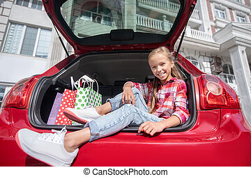 Happy moments. Smiling fair-haired girl sitting in car trunk