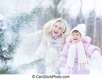 Happy mopther and kid playing with snow in winter outdoor