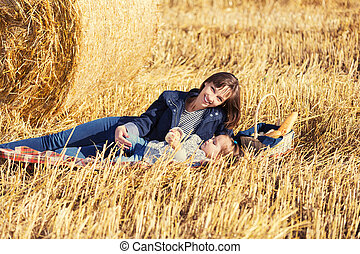 Happy mother and 2 year old girl next to hay bales in harvested field