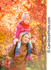 Happy mother and and smiling kid walking together outdoor in aut