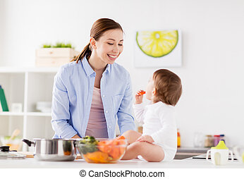happy mother and baby eating at home kitchen - family, food,...