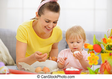 Happy mother and baby eating Easter eggs