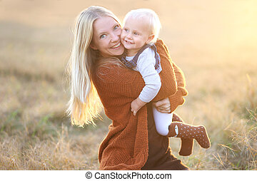 Happy Mother and Baby Girl Hugging and Playing Outside in Autumn at Sunset