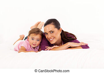 mother and baby girl lying on bed