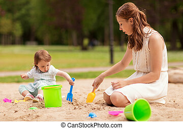 happy mother and baby girl playing in sandbox - family,...