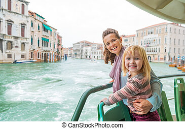 Happy mother and baby girl travel by venice water bus