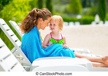 Happy mother and baby girl wrapped in towel sitting on sunbed