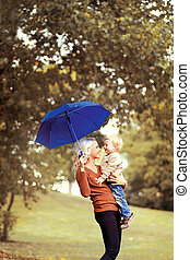 Happy mother and baby having fun in autumn day