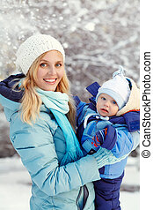 happy mother and baby in winter park