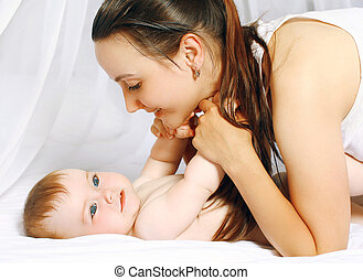 Happy mother and baby lying on bed at home