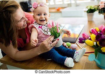 Happy mother and baby making decoration with bouquet of tulips