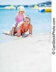 Happy mother and baby playing on sea shore