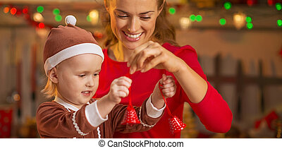 Happy mother and baby playing with christmas bells