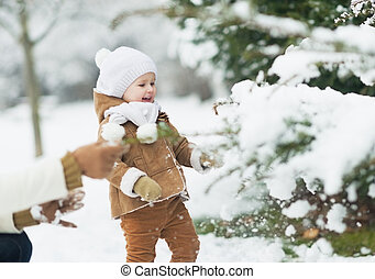 Happy mother and baby playing with snow on branch