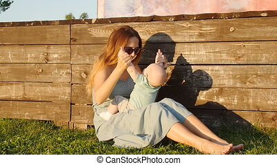 Happy mother and baby sitting on grass