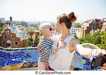 Happy mother and baby taking selfie with camera at Park Guell
