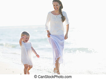 Happy mother and baby walking along sea coast
