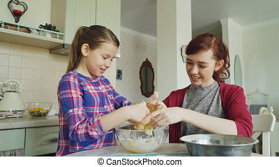 Happy mother and beautiful daughter cooking together and having fun. Mom taking off sticky dough from girl hands and laughing together. Family, food, home and people concept