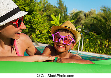 Happy mother and boy wearing sunglasses in pool