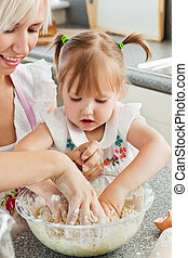 Happy mother and child baking cookies in kitchen
