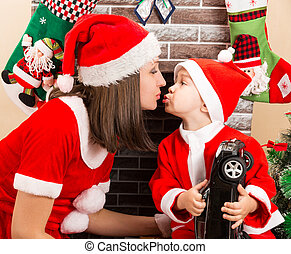 Happy mother and child boy cuddling  dressed costume Santa Claus by fireplace. Christmas and New Year.
