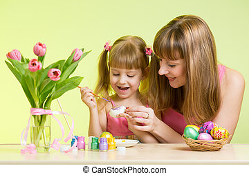 happy mother and child daughter prepare to Easter holiday with brush coloring eggs
