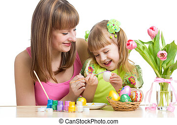 happy mother and child daughter preparing to easter holiday and with brush coloring eggs