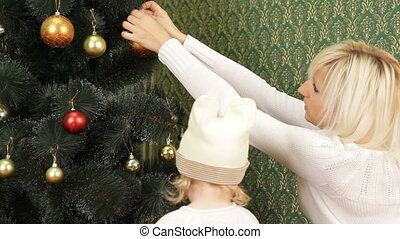 Happy Mother And Child Decorating Christmas Tree