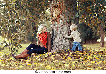 Happy mother and child having fun in autumn