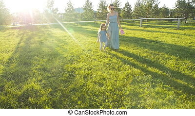 Mother and child having fun outdoor at sunset
