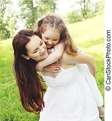 Happy mother and child having fun together in summer park
