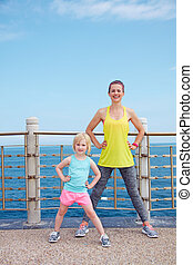 Happy mother and child in fitness outfit workout on embankment