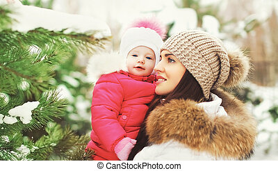 Happy mother and child in winter forest near christmas tree