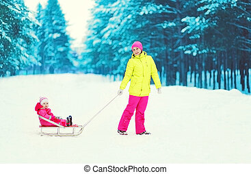 Happy mother and child on sled in winter snowy day