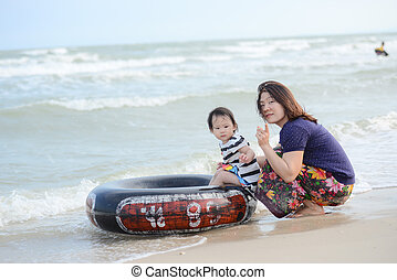 Happy mother and child on the beach.