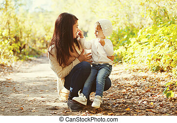 Happy mother and child playing together in autumn park