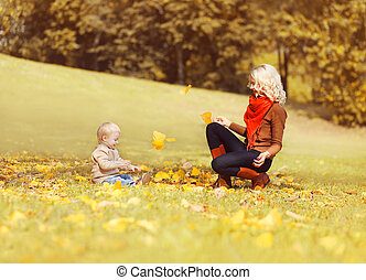 Happy mother and child playing together with yellow leafs on grass having fun in sunny autumn park