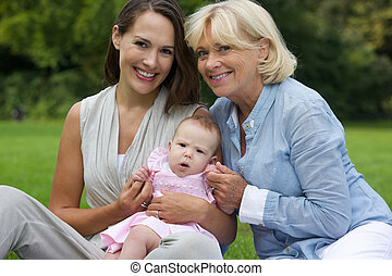 Happy mother and child sitting outdoors with grandmother