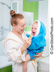 Happy mother and child teeth brushing and tongue cleaning performing