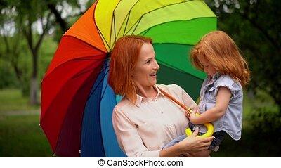 Happy mother and child under rainbow umbrella - Beautiful...