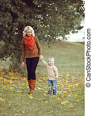 Happy mother and child walking together in the autumn park